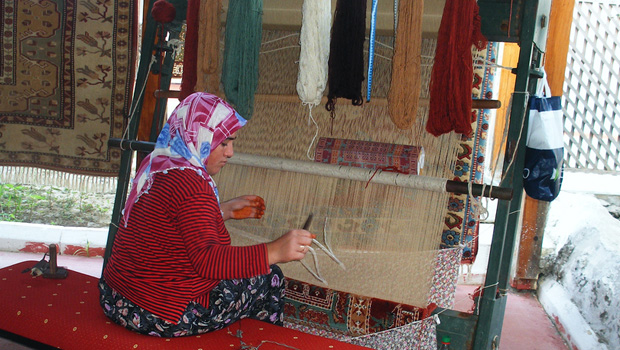 Turkish woman hand weaving a carpet